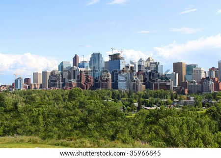 Skyline view of high rise office and apartment buildings in Calgary, Alberta, Canada with greenery in the foreground - stock photo