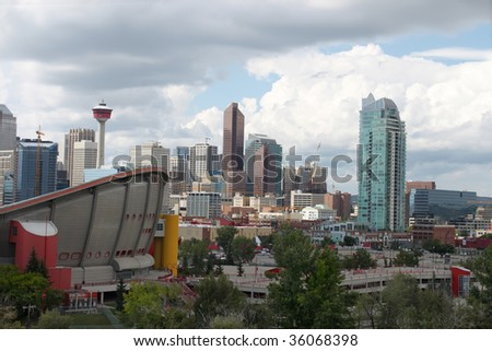 Skyline view of highrise office and apartment buildings in Calgary, Alberta, Canada with the Saddledome in the foreground - stock photo