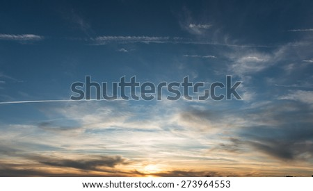 skyscape at sunset with plane  trails - stock photo