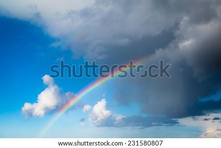 Skyscape view on blue cloudy sky with colorful rainbow. Weather. - stock photo
