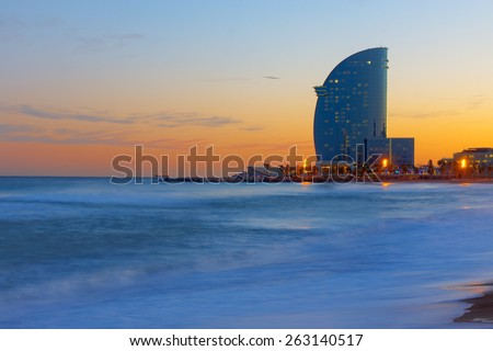 Skyscraper and beach in Barcelona at sunset - stock photo