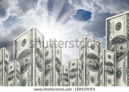 Skyscraper buildings made from one hundred dollar money banknotes on cloudy background. - stock photo