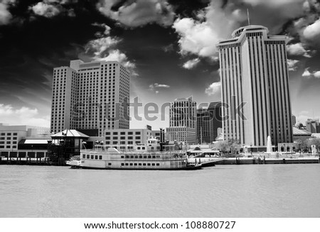 Skyscrapers and Buildings over a Brown River, New Orleans - stock photo