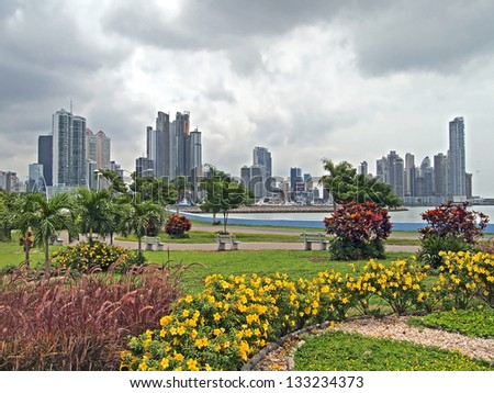 Skyscrapers in Panama City with tropical plants in foreground and stormy sky, Panama, Central America - stock photo