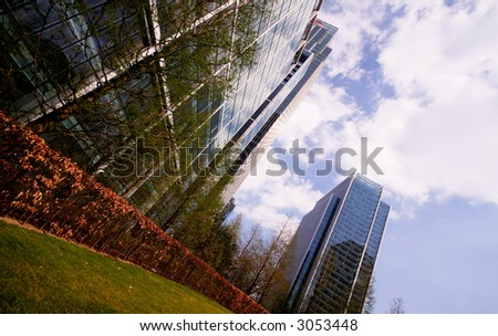 SKYSCRAPERS MIRRORED IN FRONT OF GRASS - stock photo