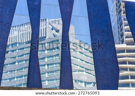 Skyscrapers, one under construction, reflected in the mirrors of a lilac wall - stock photo