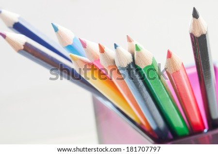 Slanting colorful wooden crayons on white background, tips of pencil, macro with shallow dof. Selective focus. - stock photo