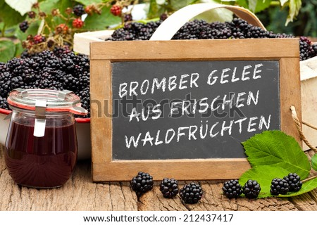 Slate blackboard with the Germans words: Brombeer Gelee aus frischen Waldfruechten (Blackberry jelly made from fresh wild fruits), in front of ripe blackberries and a on a rustic wooden table - stock photo
