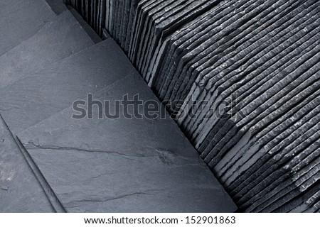 Slate roofing tiles in a pallet ready for sale sale as a construction material at a building suppliers - stock photo