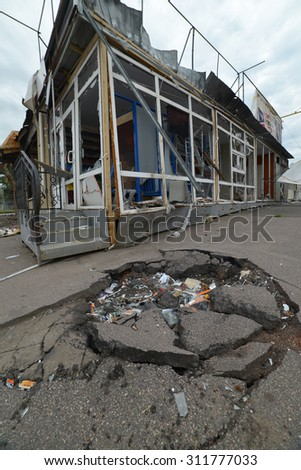SLAVJANSK, UKRAINE - JULY 15, 2014: the result of the shelling of a peaceful town militias. In the foreground a funnel from a mine explosion. - stock photo