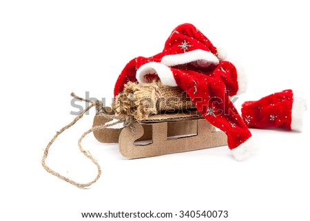 Sledge with bag and Santa Claus clothes isolated on a white background. - stock photo