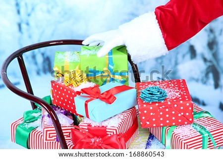 Sledge with Christmas presents, on winter background - stock photo