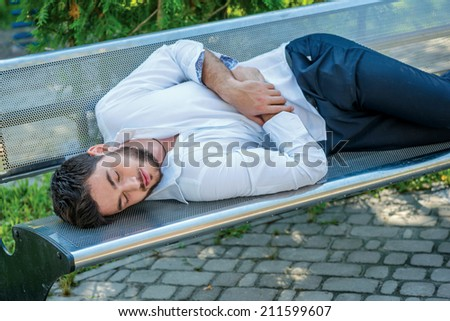 Sleep at work. Successful businessman sleeping on a bench in the park after after a hard day's work. Confident young man in formal attire and necktie. - stock photo