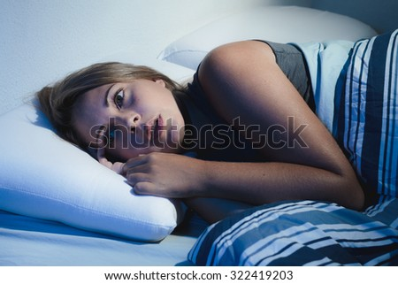 sleep disorder, insomnia. young blonde woman lying on the bed awake - stock photo