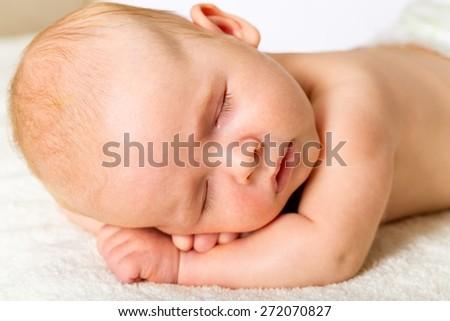 Sleeping. Adorable baby sleeping on stomach - stock photo