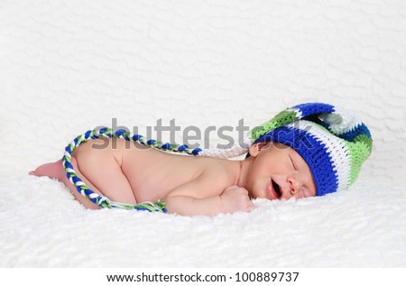Sleeping and smiling newborn wearing knitted hat - stock photo