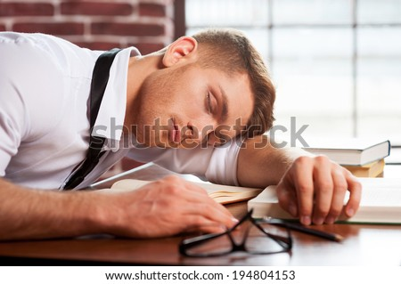 Sleeping author. Handsome young man in shirt and tie sleeping while sitting at the desk - stock photo
