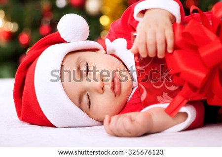 Sleeping baby child santa holding gifts and resting - stock photo