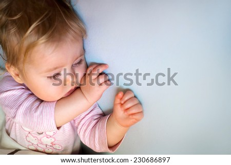 Sleeping baby girl in bed - stock photo