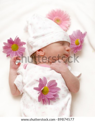 Sleeping baby girl infant with daisies on white blanket - stock photo