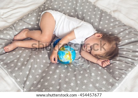 Sleeping baby holding a globe in his hands and dreaming about future travels. - stock photo