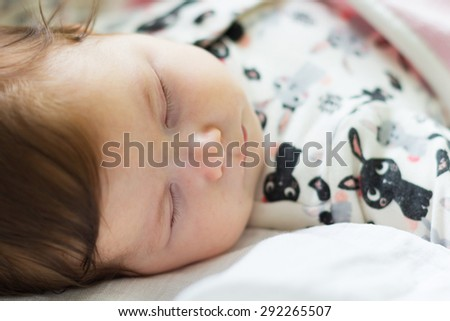 Sleeping baby lying on a bed dressed in an infant pyjamas with animal pattern - stock photo