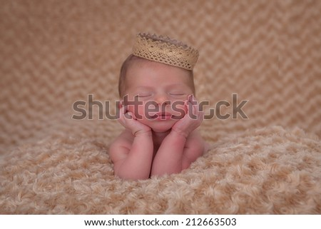 sleeping baby propped on elbows wearing crown.  - stock photo