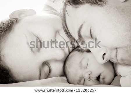 Sleeping baby with mom and dad, closeup faces - stock photo