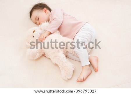 Sleeping beautiful baby toddler girl with a fluffy teddy bear on the bed - stock photo