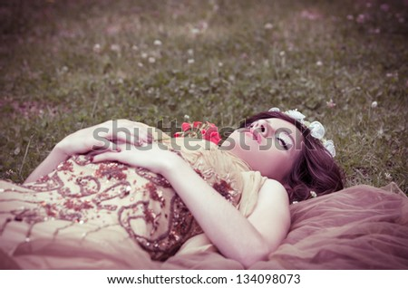 SLEEPING BEAUTY lying on the grass in the forrest with a rose - stock photo
