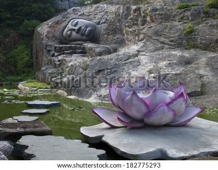 sleeping buddha statue near the lotus pond - stock photo