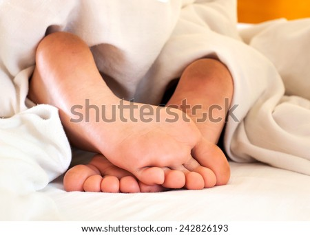 Sleeping child dirty feet on white bed linen from backside. Indoors close-up. - stock photo