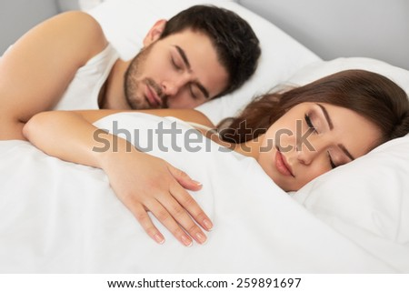 Sleeping Couple Lying in Their Bed in The Bedroom - stock photo