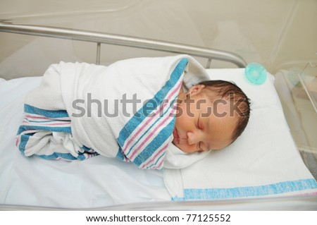 Sleeping Cute Newborn Infant Wrapped in Baby Blanket in Acrylic Hospital Bassinet just after Birth - stock photo