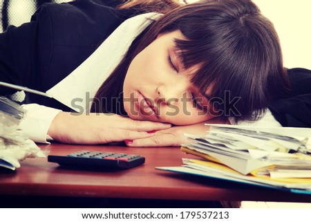 Sleeping female filling out tax forms while sitting at her desk. - stock photo