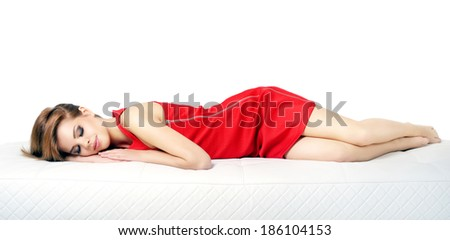 Sleeping girl on a leather sofa isolated on white background - stock photo