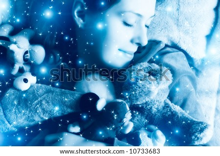 Sleeping girl with her toys. Blue tint and small fairy stars. - stock photo