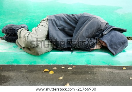 sleeping homeless man on the bench - stock photo