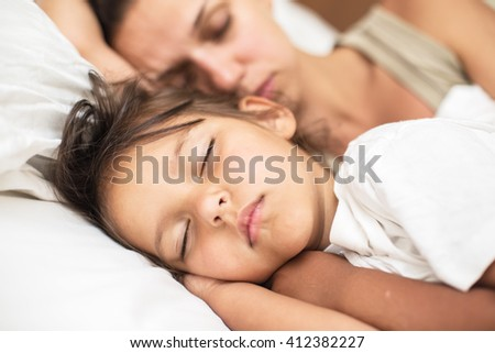 Sleeping kid girl and her mother in the bed. - stock photo