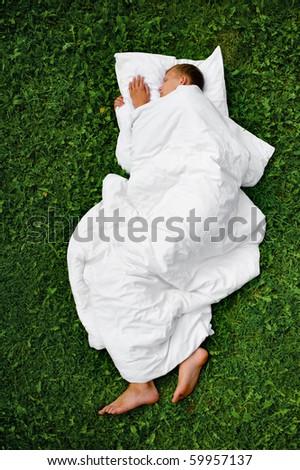Sleeping man on a grass - stock photo