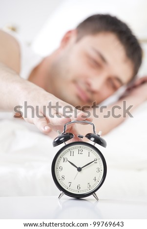 Sleeping man reaching for ringing alarm clock - stock photo