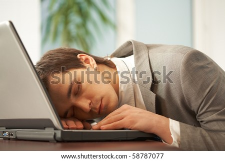 Sleeping man with his head on keyboard of laptop having rest in office - stock photo