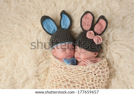 Sleeping 2 month old newborn baby twins wearing bunny costumes. They are swaddled together in a hugging position. - stock photo