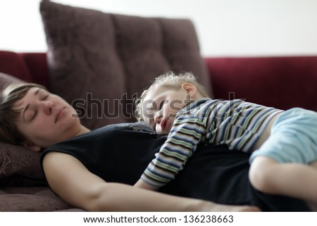 Sleeping mother and child on a sofa at home - stock photo