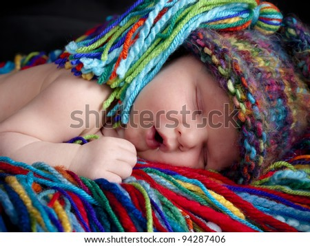Sleeping newborn baby boy one week old with blue and white hat. He is laying on a blanket of multicolored yarn. He has a matching hat. - stock photo
