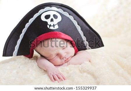 sleeping newborn baby in a pirate hat (soft focus) - stock photo