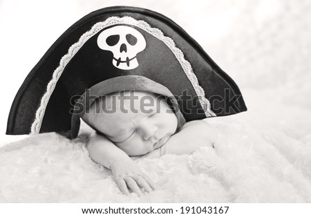 sleeping newborn baby in a pirate hat (soft focus) ( black and white ) - stock photo