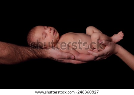 Sleeping newborn baby in her arms mom and dad. Concept of love, protection of children. Studio, black background - stock photo