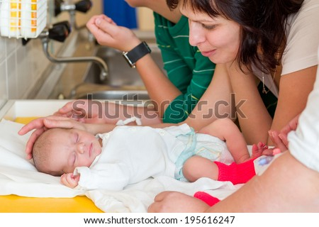 sleeping newborn baby in the hospital - the first hours of the new life, family looking to infant - stock photo