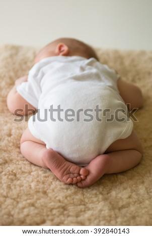 Sleeping newborn baby lying on tummy on sheepskin rug - stock photo